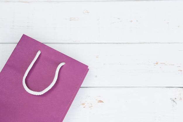 白い木製の背景の白いコピースペースに紫の買い物袋。販売購入のコンセプトです。