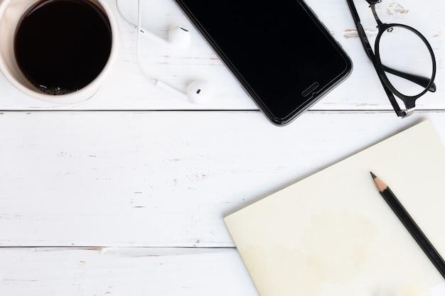 ノートブック、スマートフォン、メガネ、鉛筆、トップビューで木製のテーブルの表面