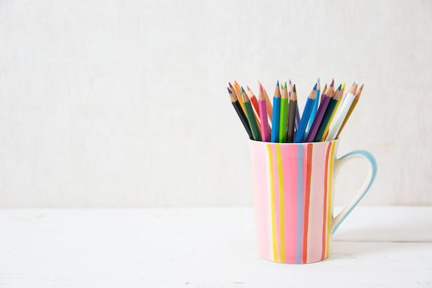 Цветные карандаши натюрморта в красочной чашке на деревянном столе