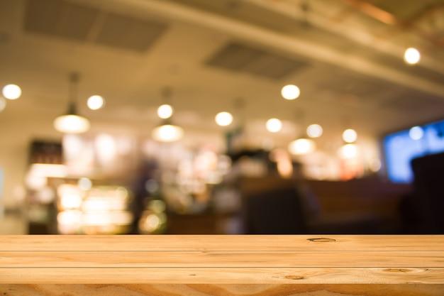 空の木製テーブルの上はコーヒーショップの背景をぼかし。商品展示モンタージュの準備ができて