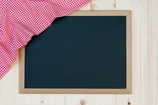赤のチェック布と黒板