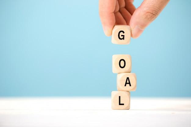 手は目標という言葉で木製キューブを保持します。ビジネス成功の目標概念