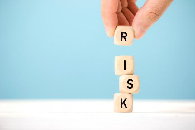 手は危険言葉で木製のキューブを保持します。リスク管理の概念