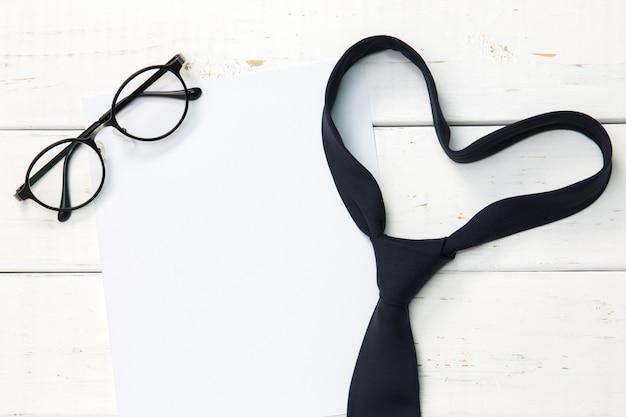 ハート形のネクタイとコピースペースを持つ木製の背景上のメガネ。
