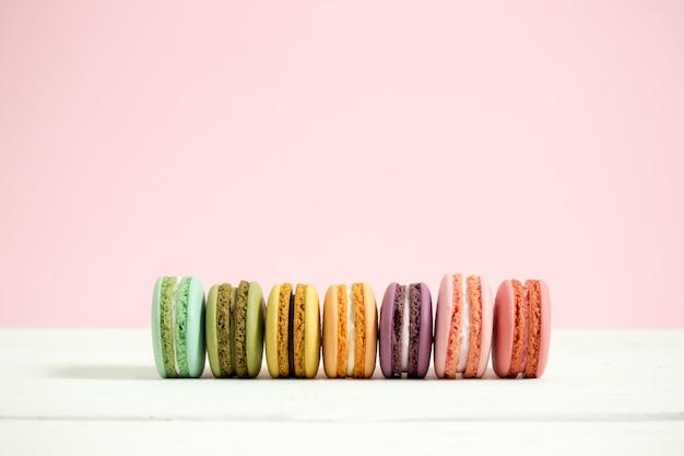 甘くてカラフルなフランスのマカロンまたは白の木製テーブルピンクの背景、デザートのマカロン。