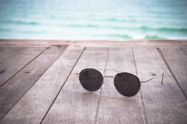 ヴィンテージの木製テーブル青い海の背景にファッションサングラス。夏休みは本当にリラックス。