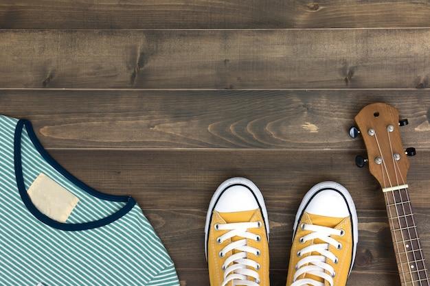 ウクレレ、シャツ、靴、コピースペースを持つ古い木製の背景に。フラットレイ