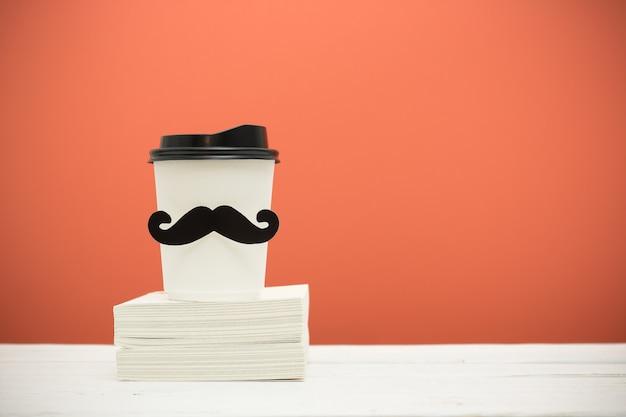 本とオレンジ色の背景上の木製のテーブルの上の口ひげとカップ。流行に敏感なスタイル。