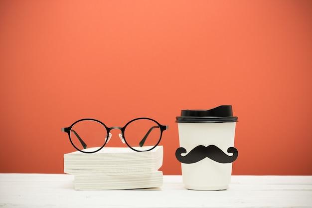 本、グラス、オレンジ色のビンテージ背景に木製のテーブルの上の口ひげとカップ