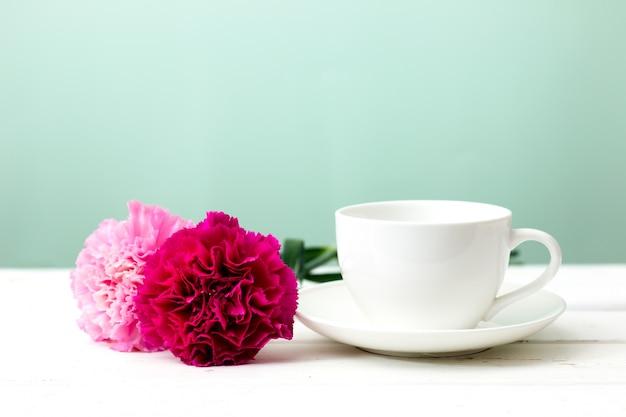 カーネーションの花と白い木製のテーブルミントの背景の上にカップ。レトロなエフェクトスタイル