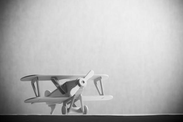 木製のテーブルの上の木のおもちゃ飛行機のイメージ。レトロスタイルの画像