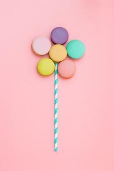 甘くてカラフルなフランスのマカロンまたはピンクの背景、デザートのマカロン。最小限の概念