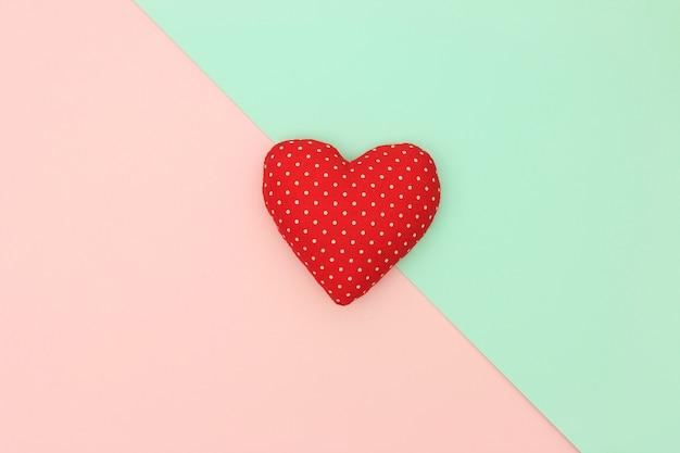 パステル調の背景にコピースペースと赤いハート。愛とバレンタインの日の概念。最小限のスタイル