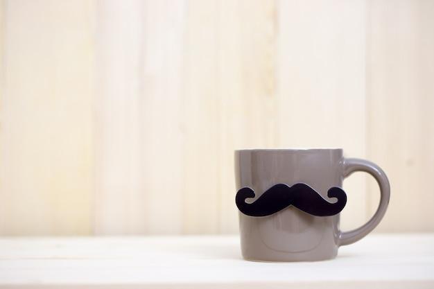 コーヒーカップ、コピースペースを持つ木製の背景に紙の口ひげ。父の日おめでとう。