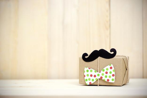 Подарочная коробка, бумажные усы, галстук на деревянных фоне с копией пространства. с днем отца.
