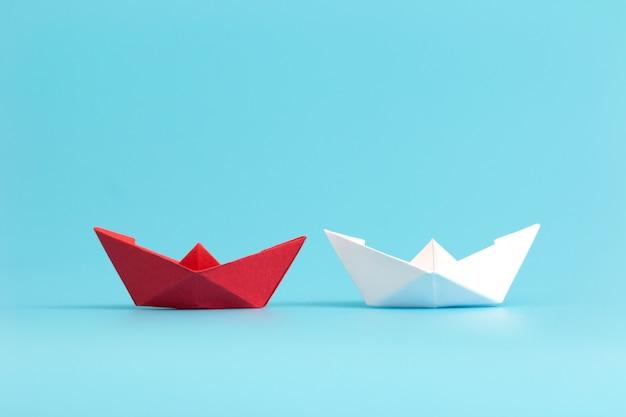 Две бумажные кораблики соревнуются. концепция деловой конкуренции. минимальный стиль.