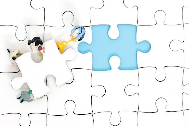ジグソーパズルを組み立てるミニチュアの人々のグループ。ビジネスチームワークの概念。