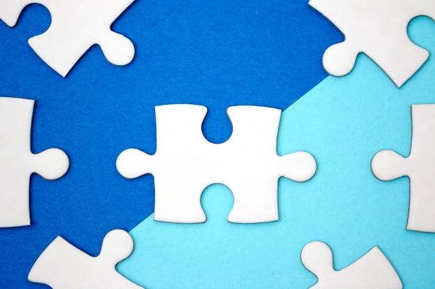リーダーシップのビジネスコンセプト - 青い幾何学の背景にジグソーパズル。最小限のスタイル平らに置きます。