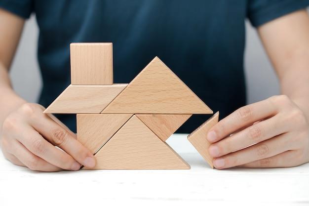 人間の手は木のタングラムパズルで家や家を建てようとします。建設コンセプト。