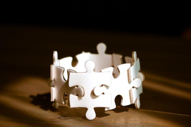 木製のテーブルの上の白いジグソーパズルのグループ。ビジネスチームワークとコラボレーションの概念。