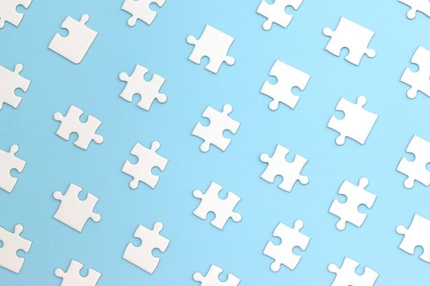 青色の背景に白のパズルのピース