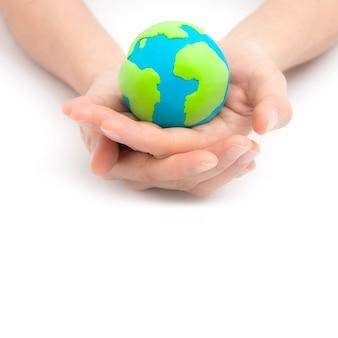 手と地球の白い背景で隔離。コンセプト保存緑の惑星。