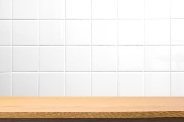 ぼやけた正方形のセラミックタイル壁に空の木製テーブル