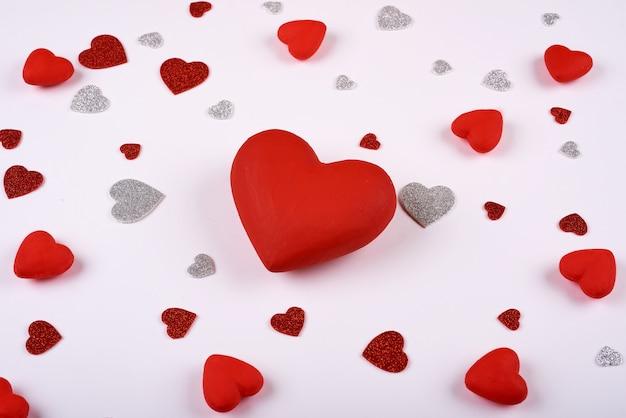 Красные и серебряные сердца на белом фоне вокруг большого красного сердца. день святого валентина.