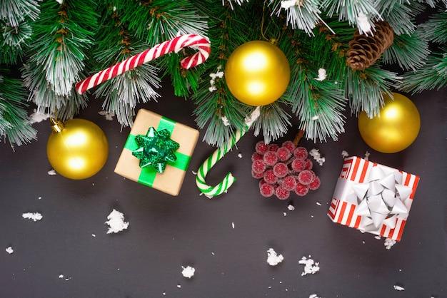 メリークリスマスまたは新年あけましておめでとうございますフレーム構成。モミの枝、クリスマスのおもちゃ、ギフトボックス、ふわふわの雪、松ぼっくり、キャンディ、黒い背景に冬の果実。フラットレイアウト、テキストのコピースペース。