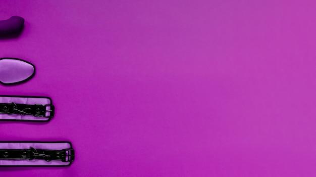 Наручники и спальная маска на ярко-фиолетовом фоне