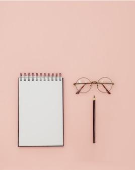 スパイラルスケッチブックメガネと黒の鉛筆。教育の概念