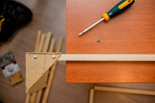 Белые европейские руки человека с отверткой, работающей с древесиной и винтами.