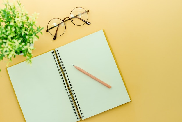 鉛筆、メガネ、ベージュの抽象的な背景のメモ帳