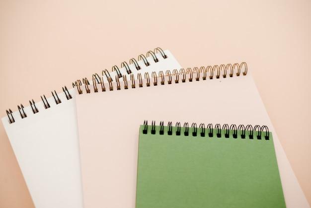 白と緑のノートブックミニマルスタイルのコピースペースとベージュ色の背景。