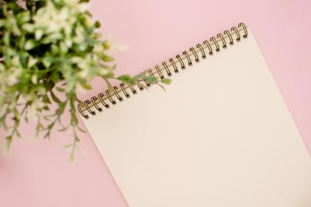 メモ帳とピンクの背景に緑の植物の写真