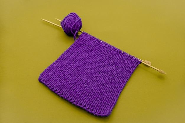 編み針と紫色のニットスカーフいくつかのオブジェクト黄色の背景