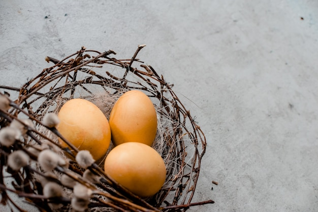 ヤナギと巣といくつかの卵がスティックします。抽象的な灰色の石の背景、ハッピーイースターのコンセプト