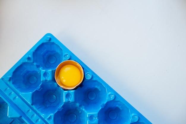 鮮やかな青い容器の角の割れた卵。白の抽象的な背景。卵殻と卵黄。水平トップビュー