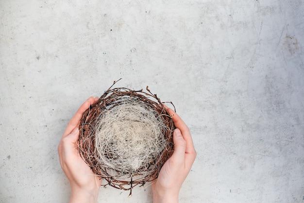 女性の手はカラフルなイースターエッグと空の巣を保持します。水平トップビューの抽象的な構成。抽象的な背景