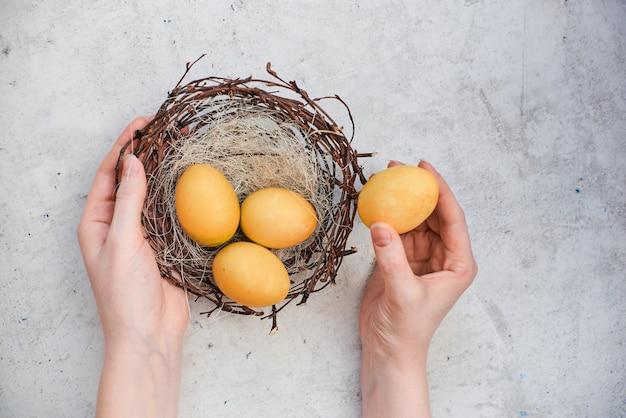 女性の手は巣と黄色い卵を握ります。抽象的な灰色の石の背景