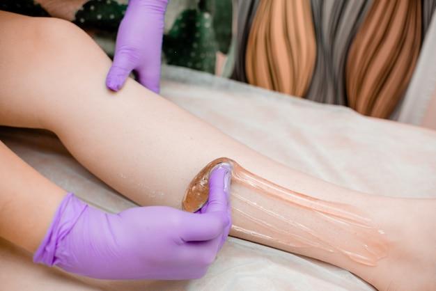 明るい紫色の手袋で髪を削除するためのワックスの蜂