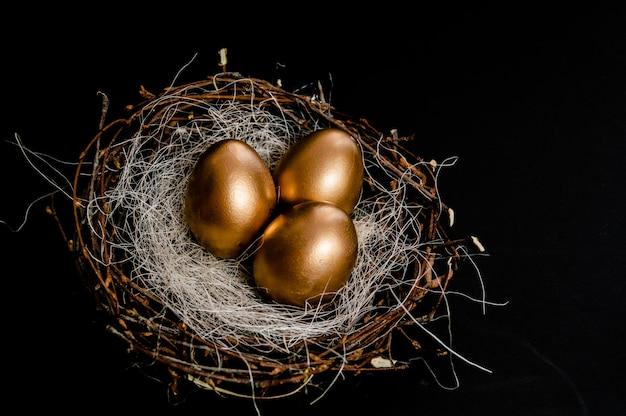 鳥の黄金のイースターエッグ黒の背景に巣