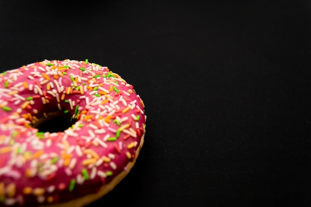 ドーナツのつや消し、ピンクの艶をかけられ、振りかけるドーナツ