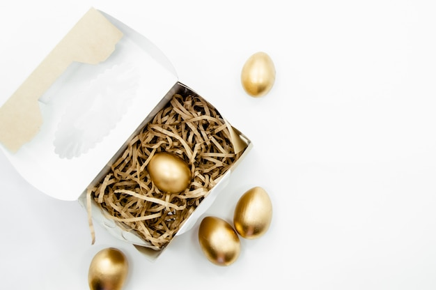 白い背景の上の金色の星とボックスの黄金のイースターエッグ