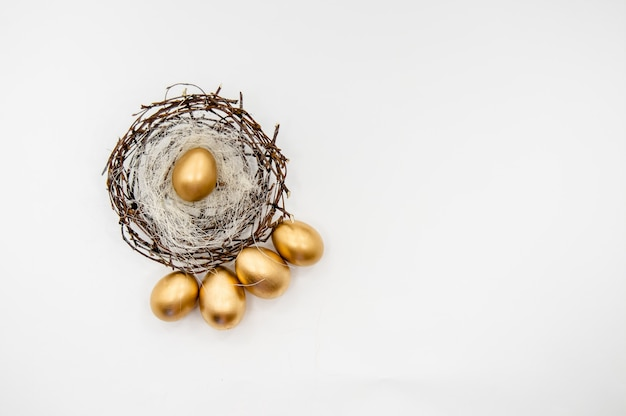 Золотые пасхальные яйца в коробке с золотыми звездами на белом фоне