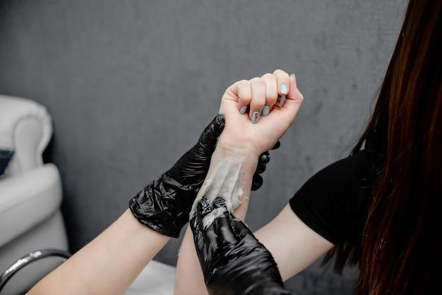 女性の手の脱毛。黒手袋スパサロンで脱毛するためのシュガーペーストまたはワックスハニー