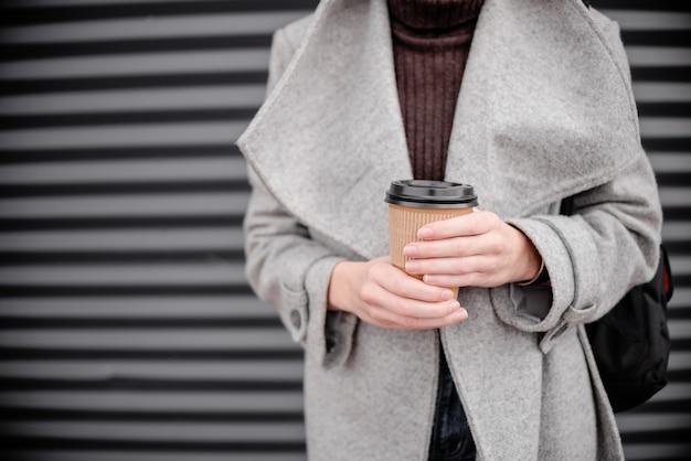 コーヒーカップ紙ラテと女性の女性の手。