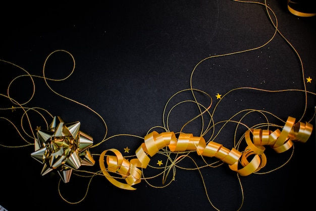 Подарочная коробка с золотым бантом на черном фоне с отделкой и блестками.