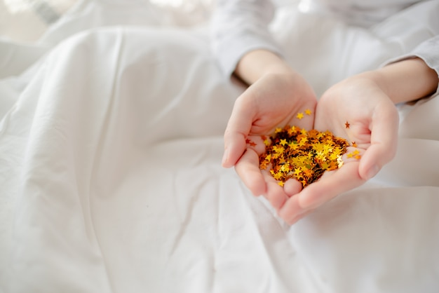 明るいお祝い金色の紙吹雪星が輝く女性の手。創造的な概念的なクリスマスホリデー誕生日パーティートップビュー