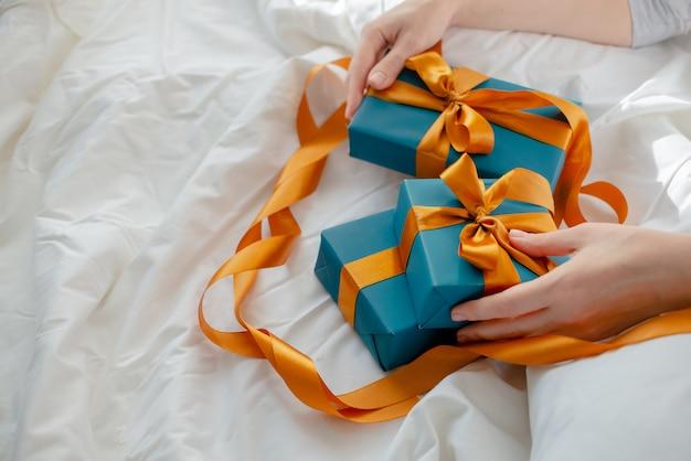 Женские руки держат подарки у кровати. новый год и рождество концепция. верхний горизонтальный вид.